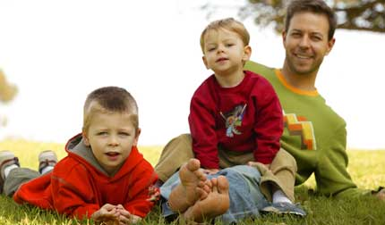 Two boys and their dad playing in the park...